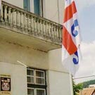 Flags and sign with greater arms in front of Surdulica municipality building